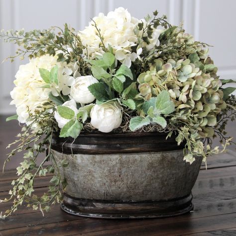 Spray paint the metal oval tin to silver and fill with fake flowers ...
