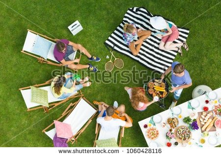 Friends Having Fun During Barbeque Party In A Park Eating Drinking Chatting And Listening To Their Friend Play Barbeque Party Barbecue Party Picnic Blanket