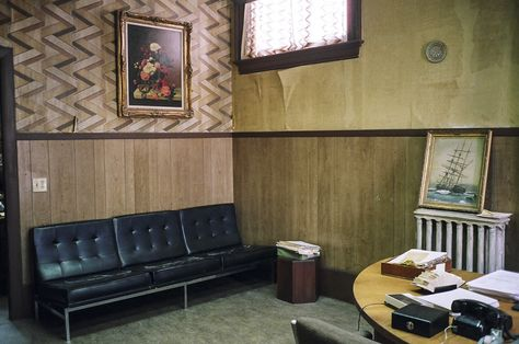Irving Office 2: Set of Irving Rosenfeld's (played by Christian Bale) office.  Shot on location in Lynn, Massachusetts.  Furnished with distressed  but stylish couch and desk and geometric wallpaper as seen in Columbia Pictures' AMERICAN HUSTLE.  Production Design by Judy Becker Photo by:  Judy Becker