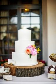 Simple white frosted cake and floral accents on a wood stump cake stand.