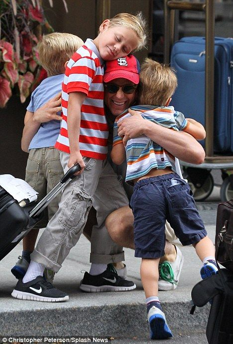 Group hug! Actor Matt Bomer gets a cuddle from his three sons, Kit, and twins Walker and Henry while his partner Simon Halls loads up the car in New York