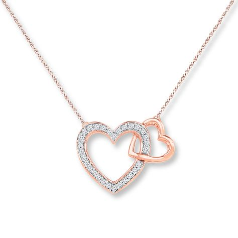 Outlined in shimmering diamonds, this heart necklace for her has a second heart of 10K white gold hugging its side. With a total diamond weight of 1/8 carat, the pendant is suspended from an 18-inch rope chain fastened with a spring ring clasp. Available online while supplies last. Diamond Total Carat Weight may range from .115 - .14 carats.