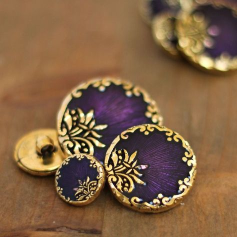Round resin button with golden metal and byzantin purple