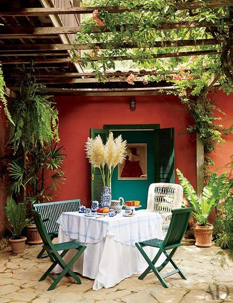 A vine-covered trellis tops a dining terrace; the artwork visible through the doors is a Fernando Botero drawing of a woman in a Valentino dress.