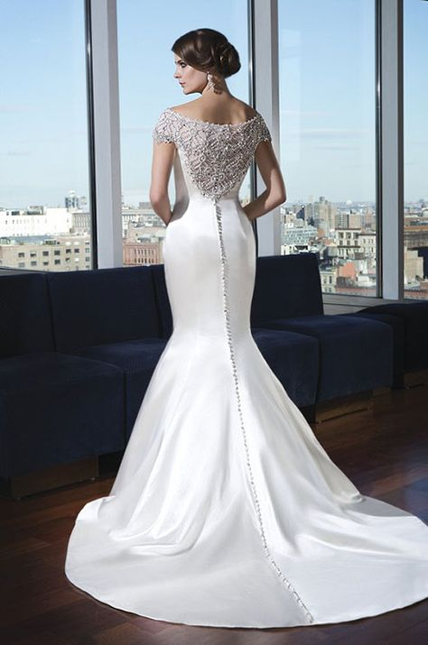 The beading continues throughout the illusion back neckline and jeweled and fabric buttons trail down the chapel length train. Justin Alexander Signature, 2014
