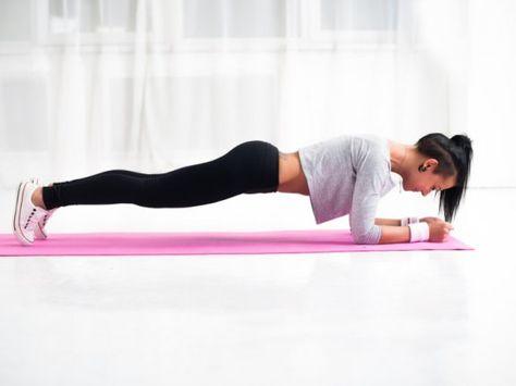 Coretraining für eine starke Mitte Trainierte junge Frau beim Planking auf einer Matte