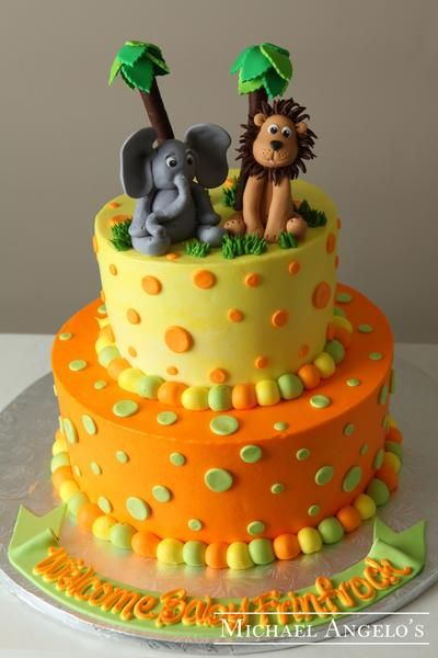 Description This cake is iced in buttercream with orange and green polka dots decorated all around. The jungle animals and palm trees are hand made from gum