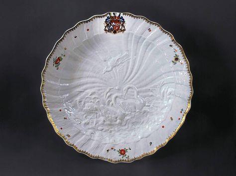 """Mit 43,5 cm gehört das Stück zu den zweitgrößten Platten des Schwanenservices. Sie zeichnet sich durch das prachtvolle, bekannte Relief aus: zwei Schwäne mit einem Fischreiher zur linken und einem weiteren darüber im Fluge. Die muschelartig modellierte Fahne mit dem Allianz-Wappen des Grafen Brühl und dessen Frau Gräfin von Kolowrat-Krakowsky bemalt sowie """"Indianische"""" Blumen und goldenem Rand.  Die Platte wird in den Arbeitsberichten Kaendlers in den Jahren 1738 / 39 erwähnt."""