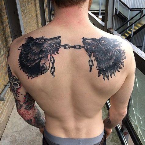 Tatuagem masculina de lobos nas costas.
