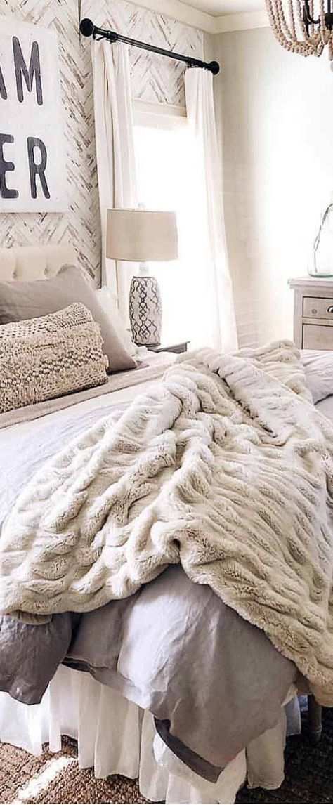 Farmhouse bedrooms should have plenty of texture in not only textiles but in the furniture and accessories as well. Be sure to include natural fiber rugs, cozy knitted blankets, and faux fur pillows. Wicker and rattan complement this design aesthetic a few beautiful baskets or rattan accent chairs add warmth and charm. #farmhouse #farmhousestyle #countrybedroom #farmhousemasterbedroom #decoratingideas #masterbedrooms #masterbedroomideas