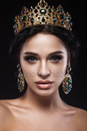 Beautiful brunette girl with a golden crown, earrings and professional evening make-up. Beauty face - Buy this stock photo and explore similar images at Adobe Stock