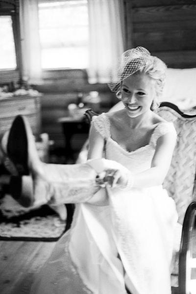 Elegant western bride pulling on her wedding boots