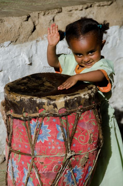 little girl playing large colorful drums, Gondar, Ethiopia, 2012