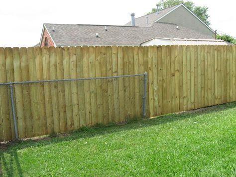 In front of a cross-tie board fence in a front yard.