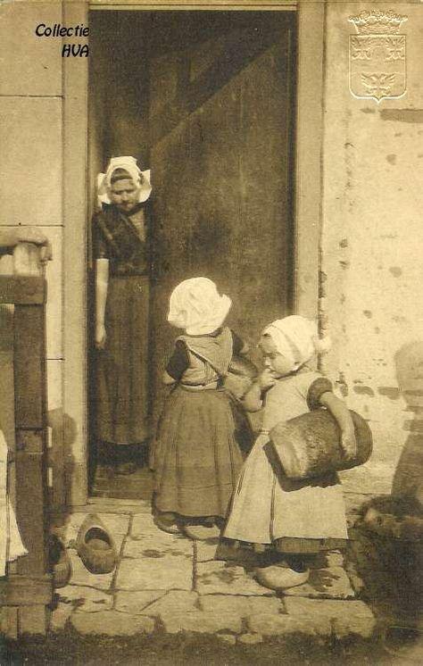 Terug van de bakker / back from the bakery, ca. 1910. Twee meisjes in klederdracht met elk een 8-ponder brood onder de armen.