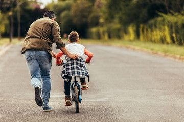 Man Helping His Kid In Learning To Ride A Bicycle Sponsored