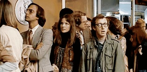 """A still from ANNIE HALL, as Annie and Alvy wait to get into a movie. Cognoscenti know a man who thinks he's a film maven starts talking pompously about Marshall McLuhan, causing Alvy to roll his eyes. Lo and behold, McLuhan shows up and chews out the jerk, telling him, """"You know nothing of my work."""" Ah, if only life really worked this way!"""