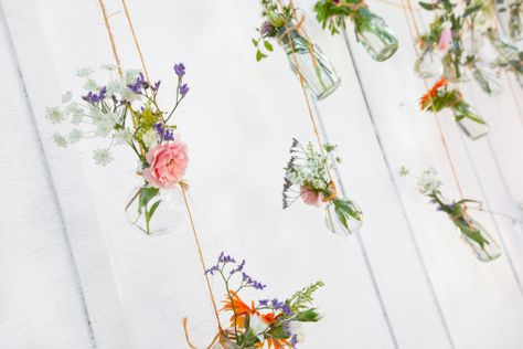 For a twist to your typical flower vase, string small mason jars together and hang them against an empty wall. Pick your favorite flowers and create beautiful arrangements for each jar.