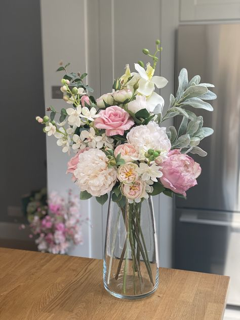 White and pink silk flower arrangement made up with Peony's, Hedgerow roses, Orchids, Lambs Ear and Eucalyptus. This silk flower arrangement is available with or without this stunning glass vase and can be set in artificial water. Arrangement is approximately 60cm tall at the highest stem tips. Vase measures 30cm in height. Please note, as our flower arrangements are handmade there may be a slight variation to the product images shown. All arrangements are made to order and require a 2-3 week pr