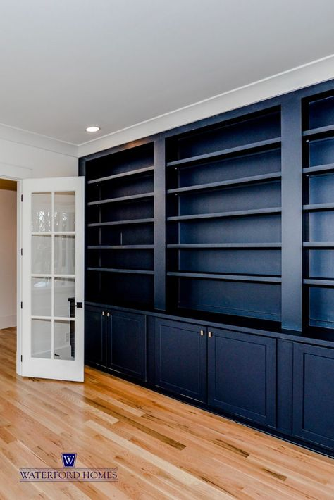 A bold navy blue built-in bookcase makes this modern farmhouse home office pop. The built-in shelving and cabinetry is both functional and stylish. Glass french doors lead into the office. #homeofficeideaslayout #homeofficeideasonabudget #Modernhomeoffices #homeofficeideasorganization #Smallhomeoffices #workfromhomeofficeideas