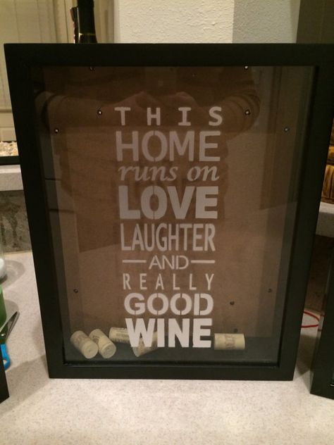 Shadow Box Wine Cork holder. Quote says This home runs on love laughter and really good wine    Black frame with metallic silver font. If you want