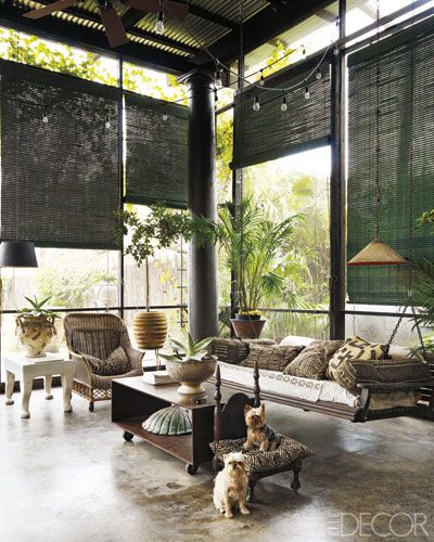 At decorator Gwynn Griffith's home in San Antonio, Texas, forest-green shades hang in the double-height screened porch. The suspended sofa and wicker chair are accessorized with pillows covered in African textiles, and the side table is by John Dickinson; stained concrete floors nod to the building's industrial past.