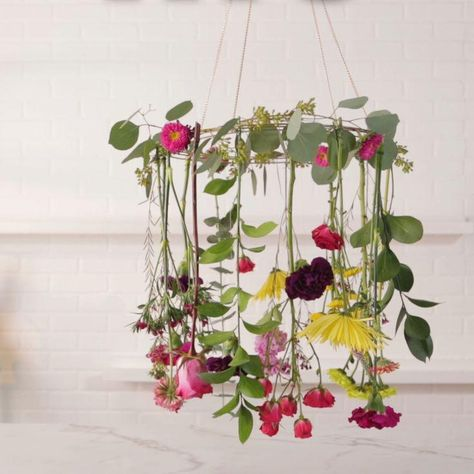Perfect for a party, this fresh flower chandelier is simply gorgeous. All you need is grocery store flowers and a few craft supplies to make it yourself. Choose a mix of bold blooms and fresh greenery for a sweet and sophisticated centerpiece. Hosting a bridal shower? Try using soft greens and white flowers! #diypartydecor #floraldecor #diyflowerchandelier #bhg