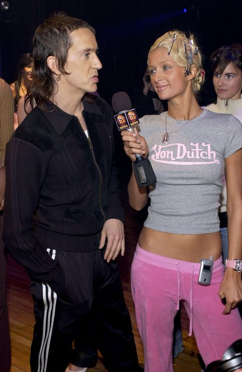 Paris Hilton interviews the designer Jeremy Scott backstage while wearing a Von Dutch t-shirt and pink Juicy Couture sweatpants with her flip phone on the belt.