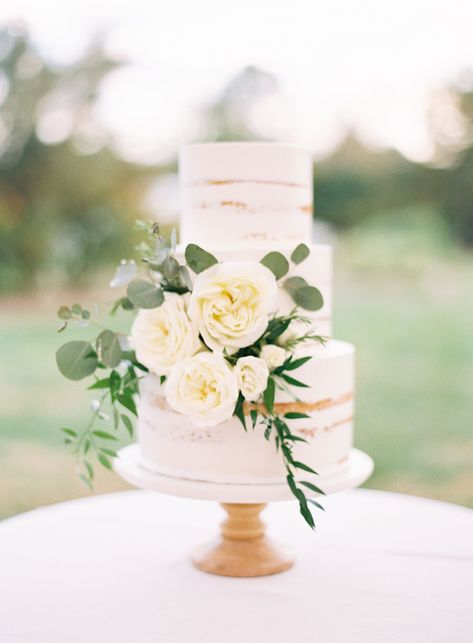 A semi-naked, champagne-flavored cake with mascarpone filling and vanilla buttercream icing gets some garden charm with white roses and eucalyptus. It's hard to envision a cake more perfect for an outdoor spring wedding! Click through to see more simple wedding cakes! #simpleweddingcakes #springwedding #springweddingcake #gardenwedding #weddingcakes