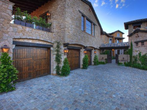 This motor court set up with its stone surface and wood garage doors is a car enthusiast's dream. A stone facade and dazzling wooden doors combine to create a stunning home exterior.