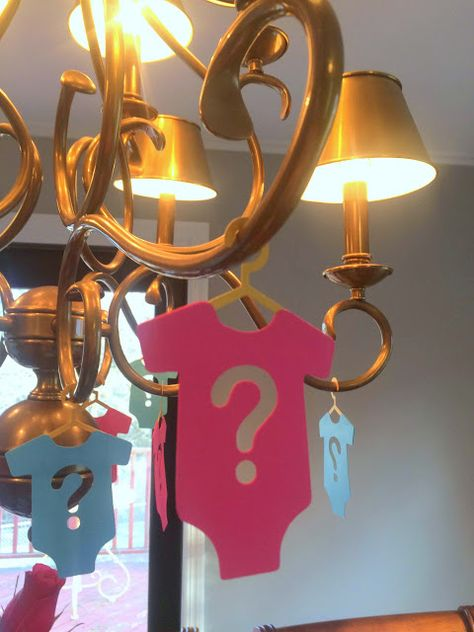 Pink and Blue Onesies to Decorate the Chandelier for Gender Reveal Party