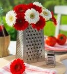Chrome grater filled with red & white flowers for Italian themed dinner table decor