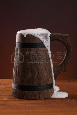 Wooden Beer Mug With Beer And Foam Standing On A Wooden Table On A