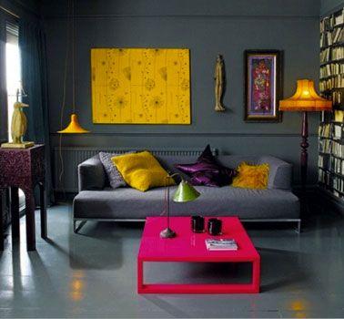 Le canapé et le mur, gris foncé, se confondent - les touches de jaune moutarde (coussins, tableau, luminaires) dynamisent l'ambiance.