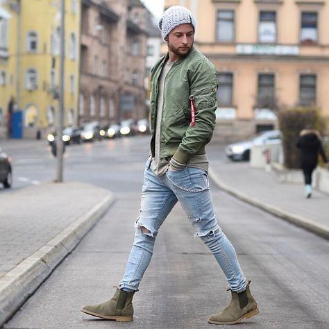 Light gray knitted slouch beanie hat, gray tee, green bomber jacket, blue j