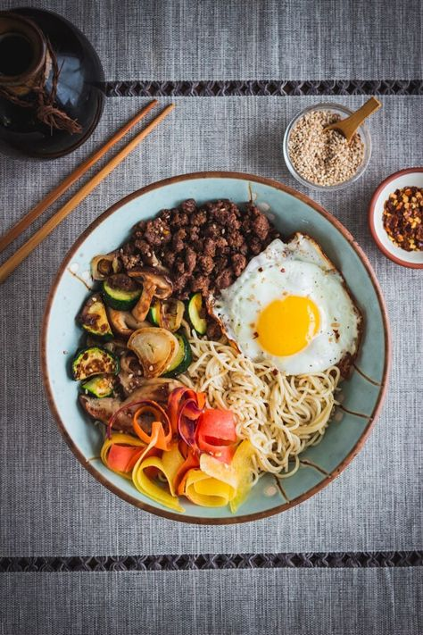 Sautéed vegetables, savory ground beef, and a fried egg are served over rice ramen, then mixed all together so the flavors and textures combine to create a gloriously tasty gluten free ramen bowl! A simple and delicious meal in less than 30 minutes! | passmesometasty.com #ramen #ramennoodlerecipes #noodlerecipes #ricenoodlerecipes #beef #glutenfreerecipes #beefrecipes #beefandnoodles #simplerecipe #passmesometasty