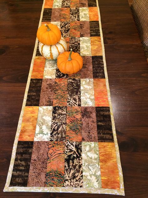 Fall colors in batik fabrics for a modern table runner design. Create a festive seasonal table with this quilted design. Table Runner And Placemats, Table Runner Pattern, Quilted Table Runners, Fall Table Runner, Modern Table Runners, Table Topper Patterns, Quilted Table Toppers, Halloween Quilt Patterns, Halloween Quilts