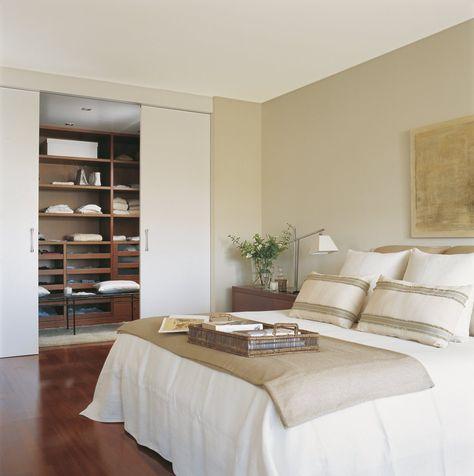 Un clóset junto al dormitorio  Se accede al vestidor con puertas correderas. Las cajas mantienen en orden las baldas superiores y los cajone...