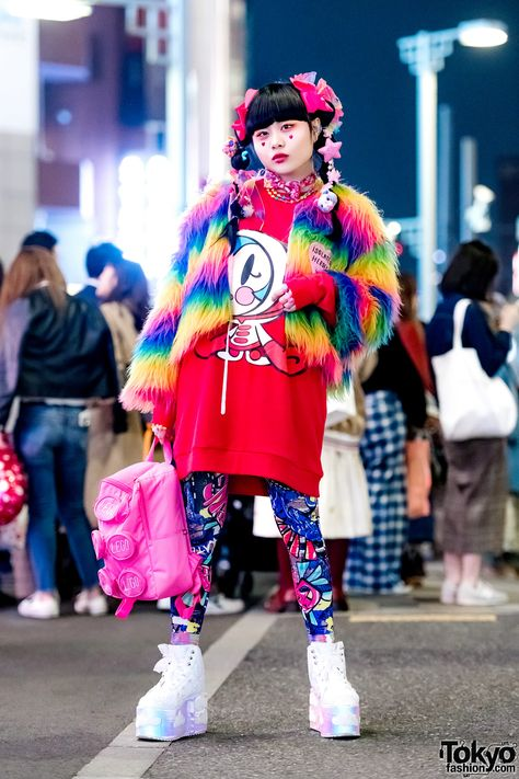 Japanese art student Chami ( on the street in Harajuku wearing a super colorful look with an Isolated Heroes faux fur jacket a Super Milk Chan top ACDC Rag graphic tights YRU cloud platforms a LEGO backpack and kawaii accessories by