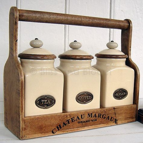   Old style ceramic cream French style tea, coffee and sugar storage jars with wooden storage rack