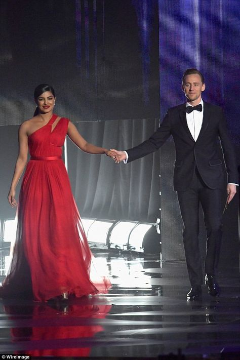 Suits you: The pair held hands as they took to the stage in their very dashing…