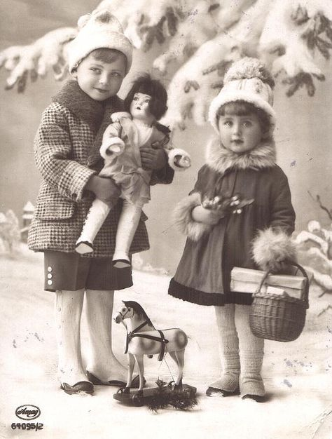 Vintage Christmas Postcard - Two sweet little girls with a big doll, a toy horse, and some other presents.