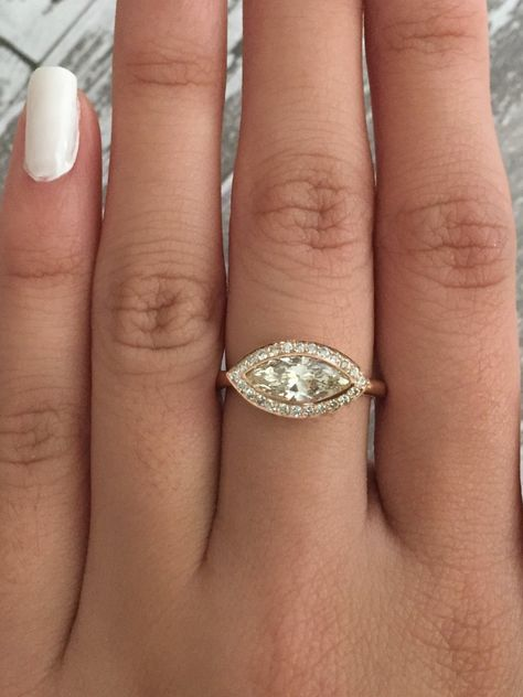 14K rose gold bezel and diamond bezel halo ring featuring a warm-hued, east-west set certified marquise briliant cut diamond measuring 10.93 x 4.78 x 2.91 mm and weighing 0.88 ct (I/SI2). The center stone is very eye clean, it's also beautifully cut. The gallery and halo are pave' set with round brilliant cut diamonds weighing 0.20 ct (G/VS2,SI1). 2 mm wide band in size 6, can be resized. *Ready to ship, EGL USA (European Gemological Laboratory) certificate and appraisal are included. SKU 16-101