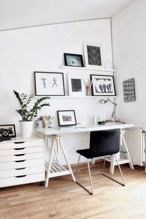 bureau scandinave blanc aménagé avec une table blanche pratique, une chaise noire, des étagères murales blanches et tableaux en noir et blanc