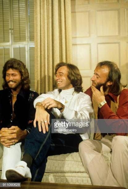 View of the pop group the Bee Gees from left Barry Gibb Robin Gibb and Maurice Gibb as they share a laugh seated on a couch 1970s #beegeesalbumcovers