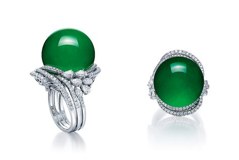 """A JADEITE AND DIAMOND RING Set with a jadeite sphere of bright emerald green colour and good translucency, measuring approximately 20. 12 mm, within a brilliant-cut diamond undulating surround, enhanced by pear-shaped diamonds on one side, to the brilliant-cut diamond shoulders, mounted in 18k white gold, ring size 7 1/4. Accompanied by report no. KJ 90398 dated 11 June 2015 from the Hong Kong Jade & Stone Laboratory stating that the jadeite is natural, known in the trade as """"A Jade"""" Sold…"""