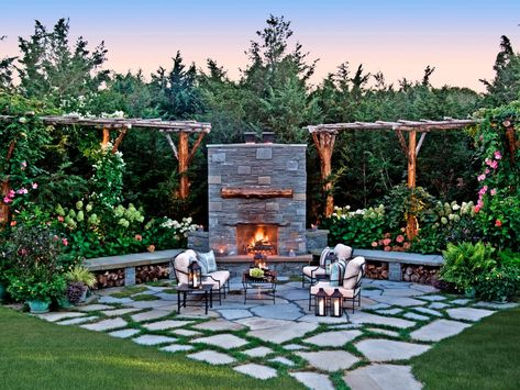 This outdoor patio features a custom stone fireplace and rustic pergolas with lush landscaping.