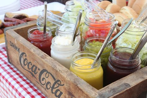 condiments and burger toppings in mason jars in a soda crate.