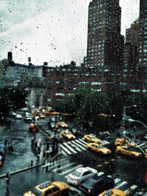 Wet window pane cars rain storm sky city street