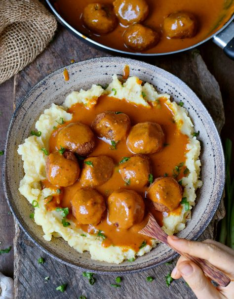 These vegan meatballs with a spicy gravy will make your mouth water. This gluten-free comfort meal is hearty, satisfying, and easy to make. The meat-free balls are perfect for dinner and meal prep as well! Enjoy these meatless balls over mashed potatoes or spaghetti. They also taste delicious with rice! #veganmeatballs #vegangravy #meatfree #meatless #glutenfreedinner #vegandinner #elasrecipes | elavegan.com